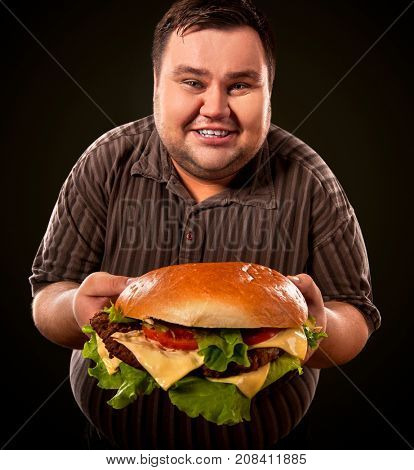 Man eating fast food hamberger. Fat person made great huge hamburger and admires him, intending to eat it. Junk meal leads to obesity. Person regularly overeats concept. Caricature of a fat man.