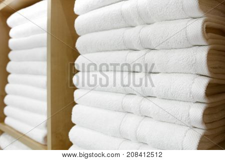 Fresh White Hotel Towels Folded and Stacked on a Shelf
