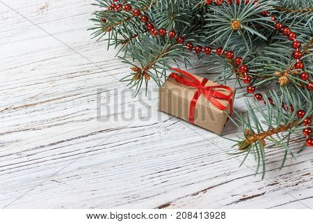 Christmas or New Year presents wrapped in natural colored paper and decorated with traditional Xmas twine and fir twigs on white background.