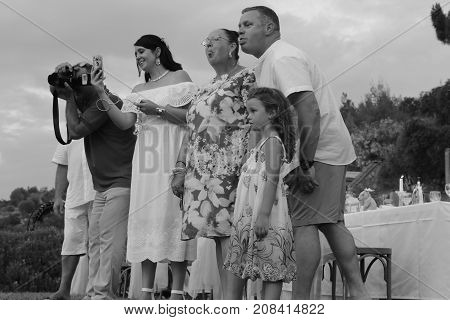 4TH AUGUST 2017,FETHIYE ,TURKEY: A photographer taking a picture of a child (unseen) with the parents and grandmother making face's to try and get the child to laugh or smile while at a wedding in fethiye, turkey, 4th august 2017