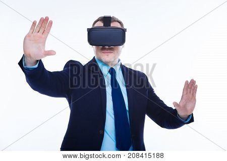 Different reality. Smart nice confident man wearing 3d glasses and moving his hands while experiencing 3d reality
