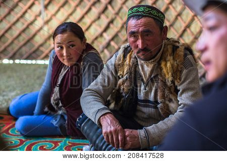 BAYAN-OLGII, MONGOLIA - SEP 28, 2017: Kazakh family of hunters with hunting birds (golden eagles) inside the mongolian Yurt. In Bayan-Olgii Province is populated mainly by Kazakhs (88,7 %)