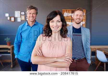 Portrait of a smiling young businesswoman standing with her arms crossed in a modern office with two male work colleagues standing in the background