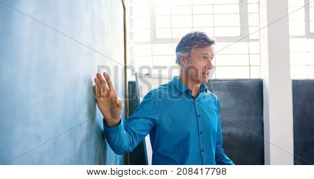 Focused mature businessman standing by a chalkboard giving a presentation in the meeting room of a bright modern office