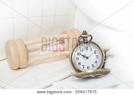 Vintage pocket watch with hourglass on white fabric background