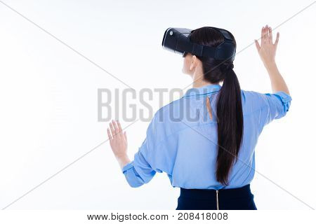 Virtual panel. Pleasant nice beautiful woman turning her back to you and touching virtual screen while being in 3d glasses