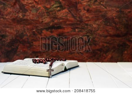 Bible and the crucifix on a white wooden table. Beautiful red wood background. Religion concept