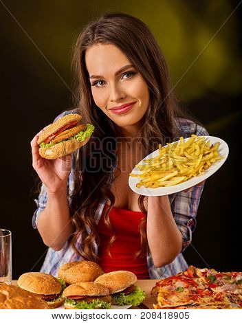 Woman eating french fries and hamburger. Portrait of student consume fast food on table. Girl trying to eat junk. Girl is having supper after hard day's work. Food semi-finished products.
