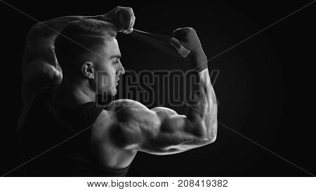 Strong man wrap hands on black background Man is wrapping hands with red boxing wraps isolated on black background Strong hands and fist ready for training and active exercise