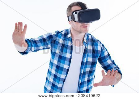 Virtual reality. Serious nice handsome man standing against white background and moving his arms it while testing virtual reality glasses