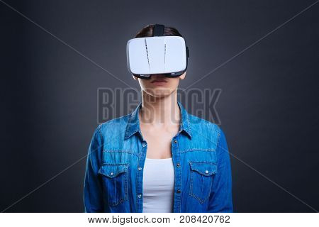 Virtual reality glasses. Serous smart confident woman standing against grey background and looking in front of her while wearing reality glasses
