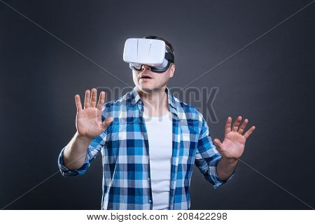 Virtual reality experience. Smart nice handsome man wearing 3d reality glasses and looking at his fingers while being in virtual reality