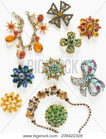 Woman's Jewelry. Vintage jewelry background. Beautiful bright rhinestone brooches, braceletes, necklace and earrings on white. Flat lay, top view.