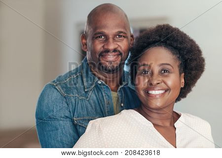 Portrait of a content African couple affectionately standing together in their living room at home