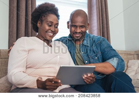Content African couple browsing online with a digital tablet while sitting and relaxing together on their living room sofa at home