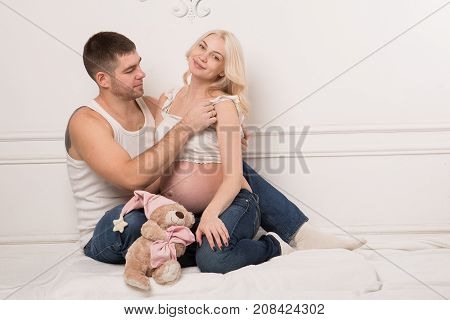 Beautiful pregnant couple in love on the background. Hands of husband on the tummy of his pregnant wife. Young man tenderly stroked pregnant belly of his wife. Husband kissing pregnant belly.