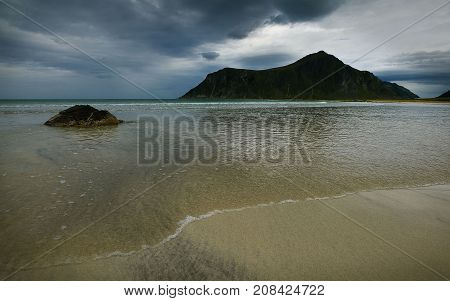 Sea landscape with mountains sand shore and gloomy sky Lofotens Norway