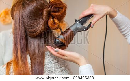Hairdresser Makes Hairstyle Girl With Long Red Hair In A Beauty Salon. Create Curls With Curling Iro