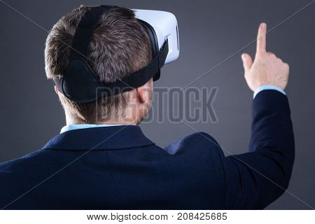 Virtual reality. Nice pleasant adult man tuning his face to the sensory panel and using it while being in a virtual reality