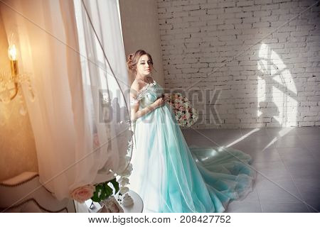 Pregnant Woman Standing At The Window In The Beautiful Azure Dress. Portrait Of A Girl Preparing To