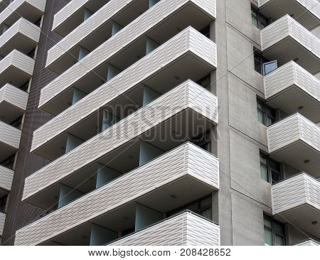modern tall white concrete apartment block with geometric angular balconies