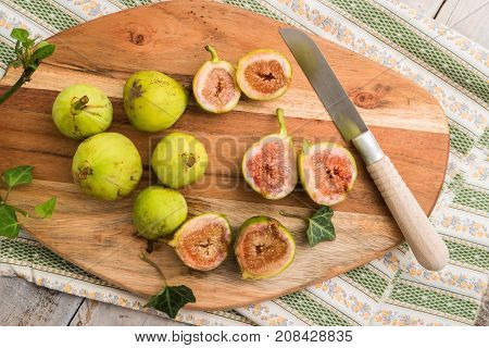 Whole figs and figs sliced in half on top of a rustic wooden table