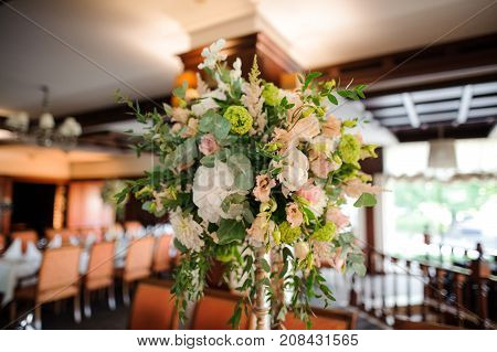 Stylish and elegant bouquet of flowers as an indoor decoration in the bright restaurant hall