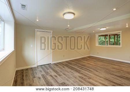 Bright Beige Large Empty Room With Hardwood Floor
