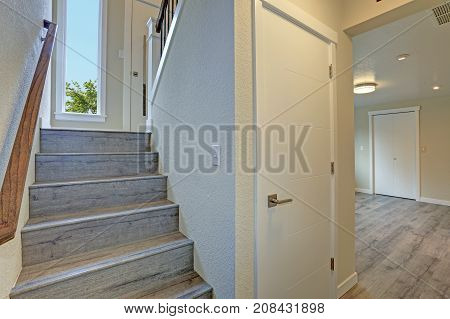 Empty Rambler Style Home Features Gray Wood Staircase