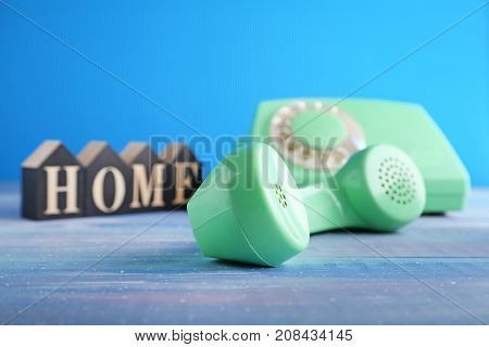 Green Retro Telephone With Word Home On Blue Wooden Table