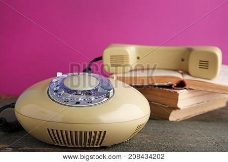 Beige Retro Telephone With Books On Grey Wooden Table