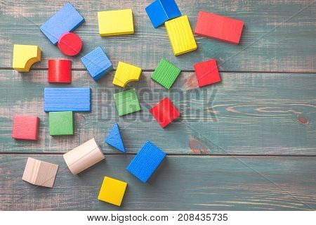 Geometric shapes for kids logical thinking. Colorful wooden blocks on green wooden background. Children's building blocks