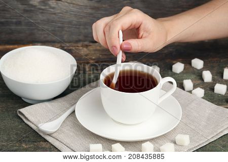 Female Hand Holding Ceramic Spoon And Cup Of Tea On Wooden Table