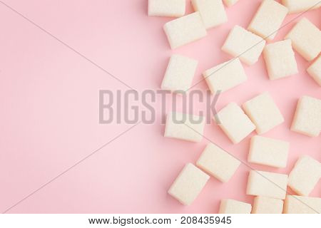 Sweet sugar cubes on the pink background