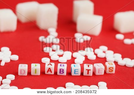 Sweetener tablets and sugar cubes with inscription Diabetes on red background