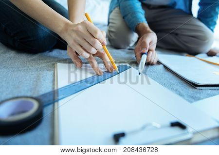 Helping is what really matters. Selective focus on hands of a young woman sitting next to her coworker and using a pencil while trying to draw a straight line in her notebook.