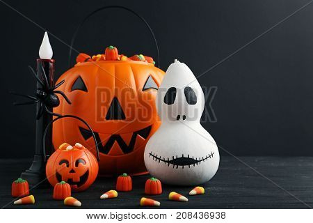 Halloween Pumpkin With Candies On Black Wooden Table