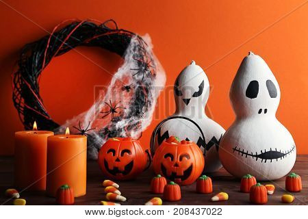 Halloween Candy Corns With Pumpkins And Candles On Wooden Table