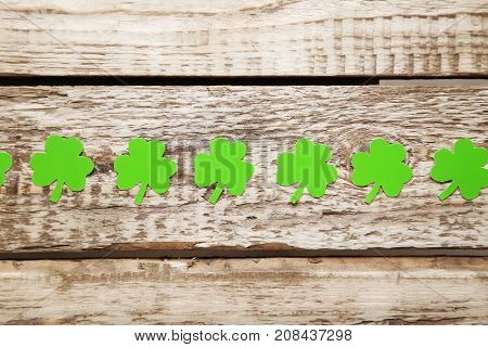 Green Paper Clover Leafs On A Grey Wooden Table