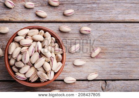 Heap Of Pistachios In Bowl On Wooden Table