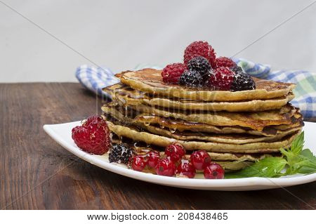 Delicious pancakes close up, with berries and maple syrup