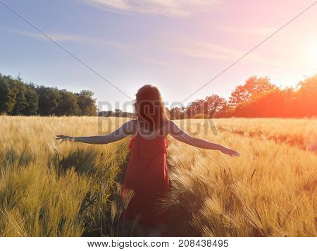 Young woman in red dress enjoying nature and sunlight in straw field