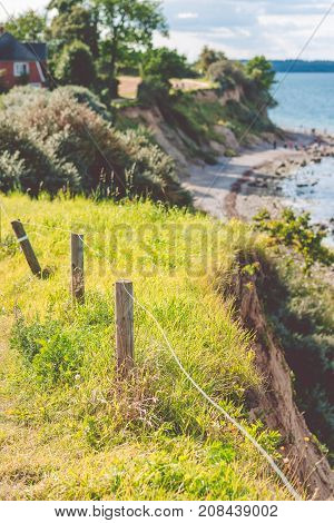 Baltic coastline. Escarpment slope lead to pebble beach. People walking along the shore hanseatic City of Luebeck - Travemuende, Germany.