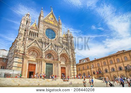 SIENA, ITALY - JULY 21, 2017: Tourists and locals next to The Cathedral of Siena (Duomo di Siena), Siena, Tuscany, Italy. The Cathedral of Siena is one of the most famous Romanesque and Gothic cathedrals in Italy