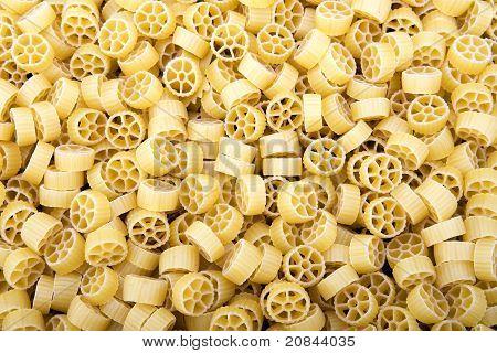 Raw Wagon wheel pasta noodles closeup macro
