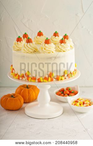 Pumpkin spice layered cake with cream cheese frosting decorated with candy, dessert for Halloween and Thanksgiving