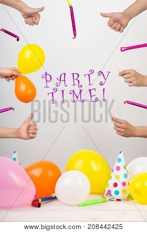holidays, celebration, occasion concept. in the center there is inscription that says party time. and around in there are lots of thumbs up, colorful balloons, birthday whistles, burning candles