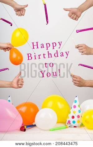 happiness, party, celebration concept. there is frame created with all attributes of birthday, ballons and candles, greeting thumbs up and whistles. in the center there is a text of congartulation