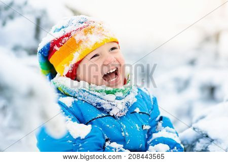 Baby Playing With Snow In Winter. Child In Snowy Park.