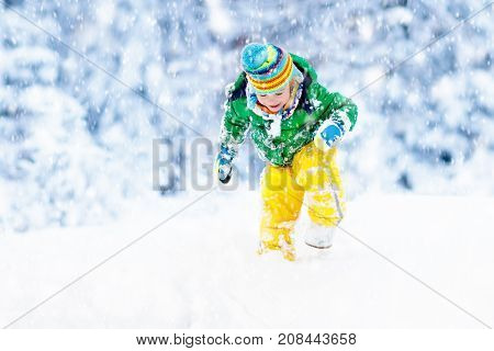 Child Playing With Snow In Winter. Kids Outdoors.